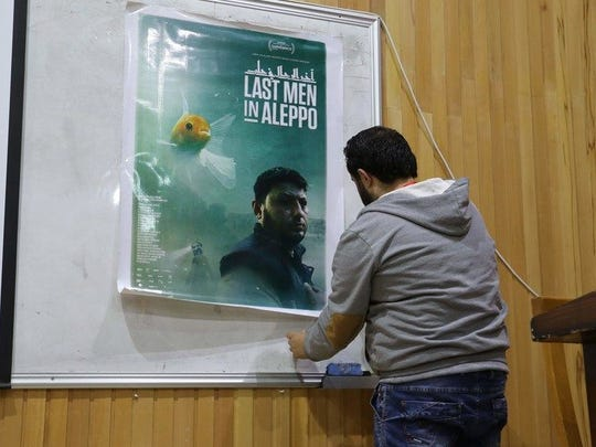 A Syrian man hangs a poster ahead of the screening