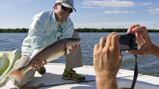 """Writer Jack Ballard, of Red Lodge, Montana, poses with his catch of the day, a 25"""" redfish, caught Wednesday afternoon in Pine Island Sound during a fly-fishing trip. Ballard was one of the members of the Outdoor Writers Association of America which met on Captiva. The group was participating in a saltwater fly-fishing outing put together by members of the Lee County Visitor and Convention Bureau."""