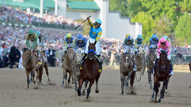 After American Pharoah crosses the finish line, jockey Victor Espinoza stands up with his whip swinging high.