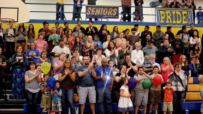 Family, friends and students give a standing ovation for Jalen Miller, a library assistant, during a surprise assembly at Gervais High School in Gervais, Ore., on Friday, May 8, 2015. Miller was diagnosed with cancer in August 2014 and has always dreamed of visiting Disneyland with her grandchildren.