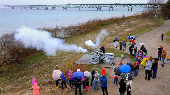 With the Mackinac Bridge behind them, historical interpreters Jim Evans and Steven Hamann educate fourth graders from Delton-Kellogg Elementary School as they fire a charge from a six-pound cannon at Colonial Michilimackinac in Mackinaw City.
