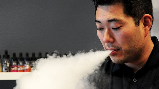 Joey Kim, owner of i-vape, exhales a vapor cloud inside his shop, on Wednesday, May 27, 2015, in Salem.