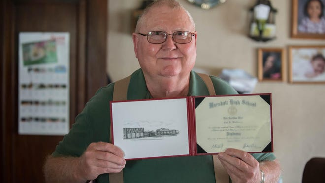 Vietnam veteran Carl Holibaugh proudly displays his high school diploma he recently received from Marshall High School.