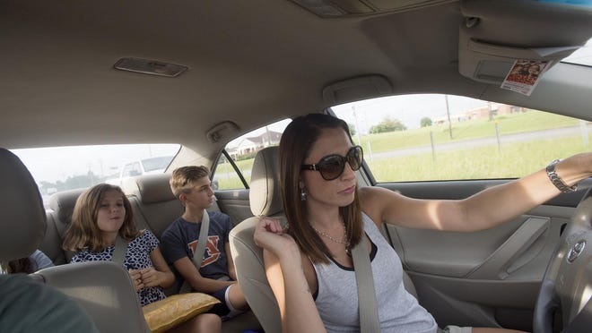 Carrie Richardson drives her son Jacob, 12, to a friend house as her daughters, Rylee, 7, and Hannah, 14, come along for the ride on Friday.