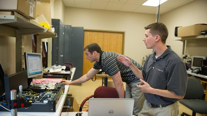 Principal Opto-Mechanical Engineer Kyle Hadock, 29, of Webster, right, works on new product testing and development with Junior Computer Engineer Jon Agins, 26, of Greece at Lumetrics in Henrietta.