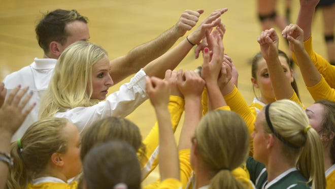 CMR head volleyball coach Theresa Besich (left, in white) huddles with her team.