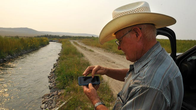 Rich Boyle, manager of the Fort Shaw Irrigation District, can use computer software and a smartphone app to take readings of the water flowing through district's irrigation channels.