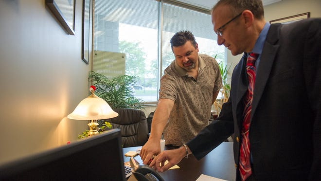 Eric Loyd, left, founder and CEO of SmartVox, works with client David Young, the managing partner of Young and Company CPAs, at Young's Henrietta office to set up his phone.