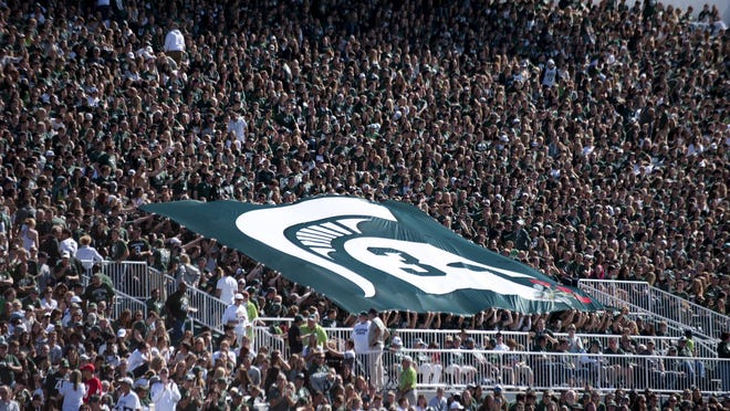 The student section holds a flag honoring former Michigan State punter Mike Sadler during halftime during the game against Wisconsin on Saturday, Sept. 24, 2016 at Spartan Stadium in East Lansing. Sadler died in a car crash in Wisconsin earlier this year.