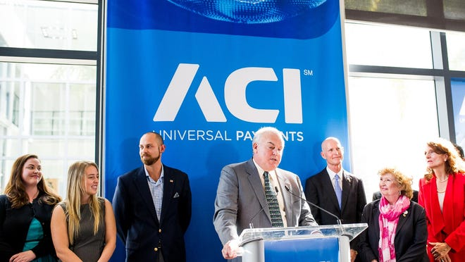 Philip G. Heasley, president and CEO of ACI Worldwide, talks at a news conference about job growth at ACI Worldwide in Naples.
