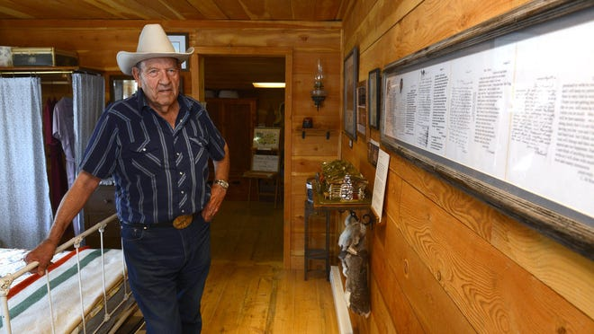 Gene Dwyer stands in the Charlie and Nancy Russell Honeymoon Cottage in Cascade on Monday. Dwyer restored the cottage to its original state and offered tours by reservation. The cabin is now for sale.