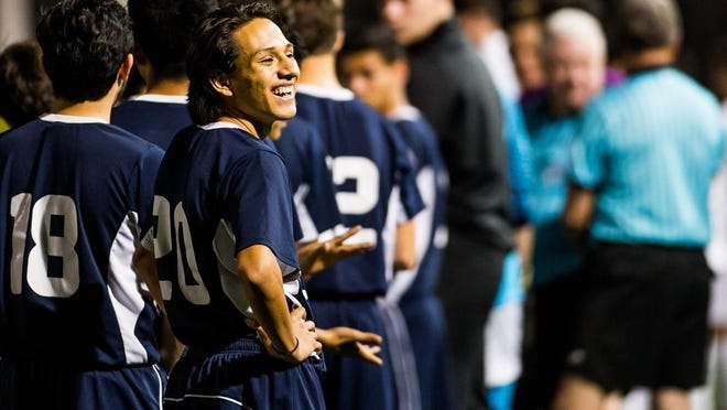 Estero High School's Jesus Frausto laughs at a teammate before the start of a 4A-12 title game against Gulf Coast High School in Naples on Friday.
