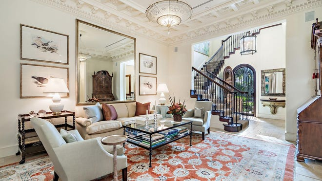 With an intricately detailed ceiling, the living room of a townhouse at 331 Australian Ave. in Midtown Palm Beach is open to the foyer, which doubles as a stair hall. With about 5,000 total square feet, the townhouse is priced at $6.28 million. [Photo by Giles Bradford, courtesy Douglas Elliman].