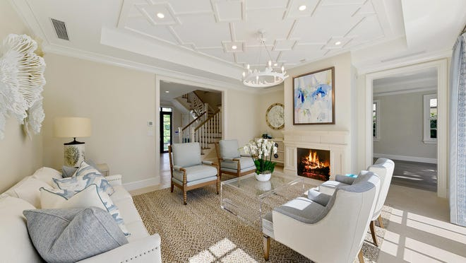 A gas fireplace is featured in the living room of a newly completed house listed at $6.85 million at 232 Bahama Lane in Palm Beach. The staircase can be glimpsed through the center doorway.