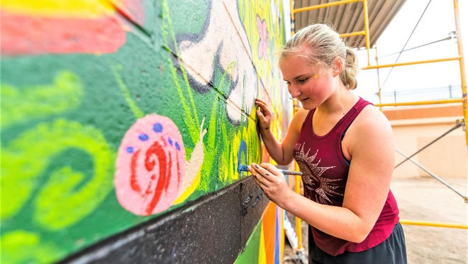 Emily Brunner, 12, paints details on a mural as part of the 2020 SAGE Art Academy Mural Camp.