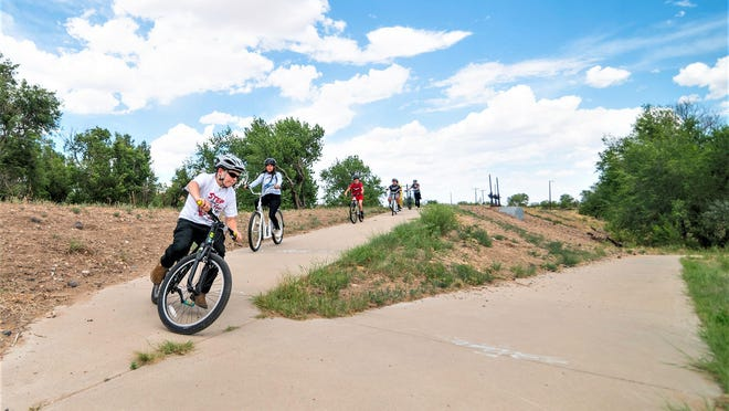 "Members of the Boys and Girls Clubs of Pueblo County known as ""Rocky's Riders"" pull into Runyon Lake after a trek from SRDA on Union Avenue."