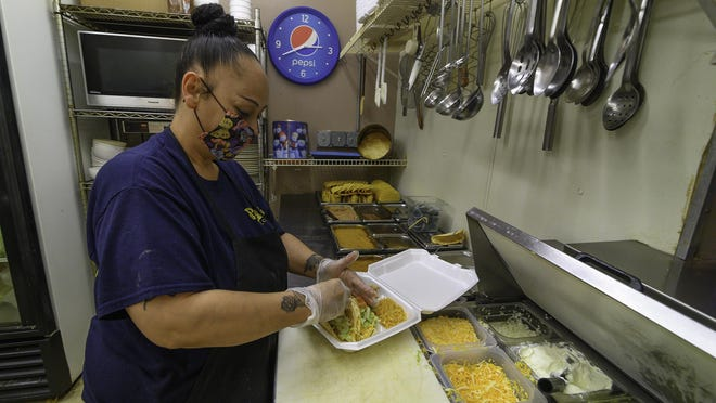 Narcisa Naranjo puts a meal together for a customer at Papa Jose's Union Cafe on Tuesday.