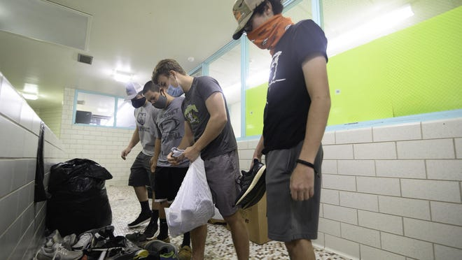 From right, Reese Bucciarelli, Colin Raper, Sean Ortivez, and Nic Colletti search through a pile of shoes for their pair as students were let into Pueblo County High School to pick up belongings last month.