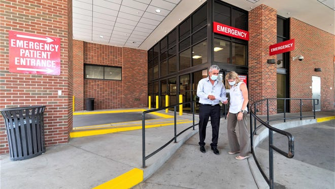 Vince Velasquez, left, and Rachael Morris, of Parkview Medical Center, converse outside the new emergency department entrance.