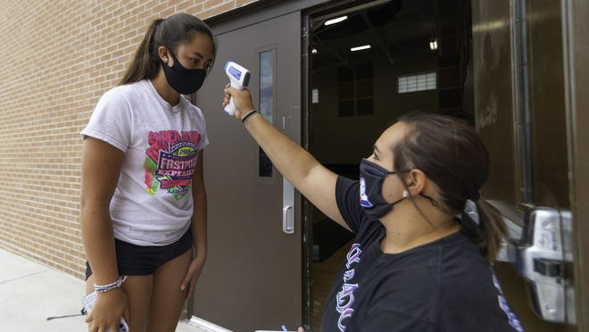 Pueblo County High School sophomore Raquel Tapia, left, gets her temperature taken by volleyball coach Carlee Chain before being let in the gymnasium for practice on Thursday at Pueblo County High School.