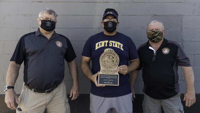 Bill Bragg, left, and Tom Cortez of the National Wrestling Hall of Fame Colorado Chapter present the wrestler of the year award to Andy Garcia on Wednesday outside of the Colorado Movement Company gym.