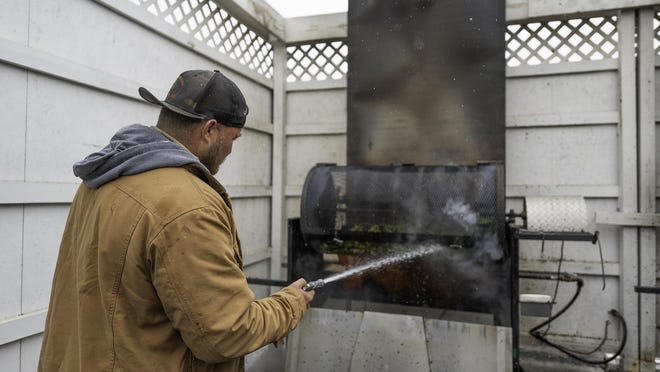 Rocky Musso roasts a bushel of Pueblo Chiles as snowflakes fall on the St. Charles Mesa Wednesday.
