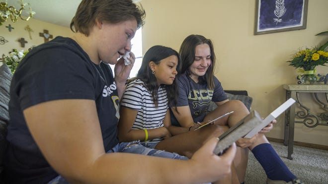 Serenity Nailor-Lewis' stepsister K'lyn Pool, left, sister Ysabel Lewis, center, and best friend Dallas Kauffman smile and cry while looking at photos and reminiscing about the late teen on Friday.