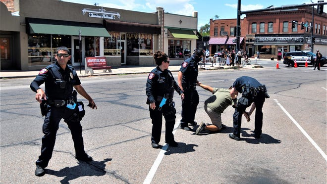 Pueblo police prepare to cuff Paul V. Romero, 42, after he caused a disturbance during the anti-Columbus demonstration Sunday.