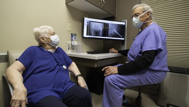 Dr. Charles Hanson, right, discusses X-ray results with patient Carole Ricotta on Thursday.