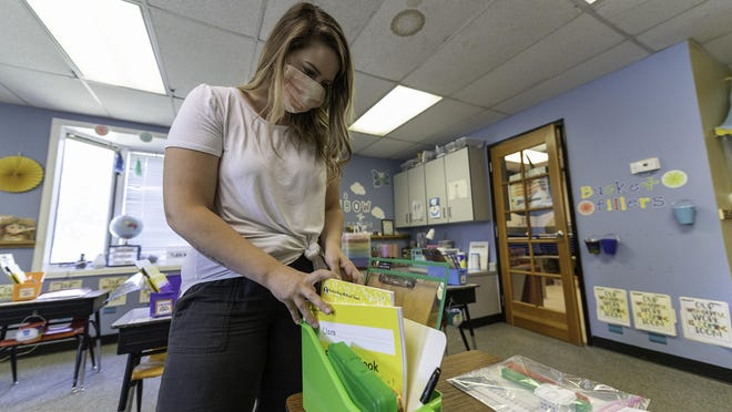 Meaghan McFarland sets up supplies for her first-grade students in preparation of reopening The McClelland School.