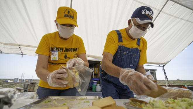 Colorado Baptist Disaster Relief volunteers Wanda Lea, left, and Ron Lea make and bag sandwiches that were delivered Friday to those displaced by the Fenix Apartments fire.