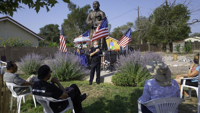 Pueblo Chief of Police Troy Davenport stands in front of the recently defaced statue of Martin Luther King Jr. and Emmett Till while addressing the crowd that gathered for a community healing event at the Friendly Harbor Community Center.