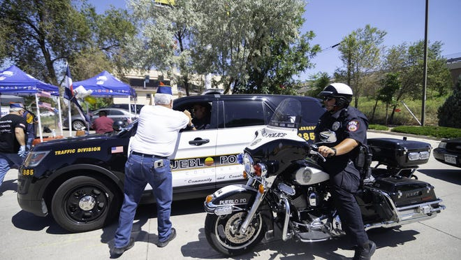 Ernesto Montoya hands meals to officers of the Pueblo Police Department during the first Curbside Essential Heroes Luncheon put on by the Pueblo Chapter of the American G.I. Forum Wednesday.