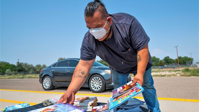Miguel Burgos picks out books for his three children at Liberty Point International. Free books were distributed to families as part of a partnership between Pueblo County School District 70, EVRAZ Rocky Mountain Steel, First Book Foundation and EPIC.