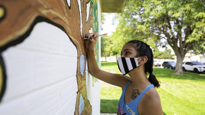 Melanie Alphin adds a tree of life to the Vinewood Park mural on Friday.