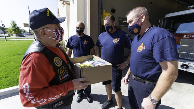 Mark Trent, left, of American Legion Post 2, delivers lunches to, left to right, Capt. Jeff Myers, DeWayne Hall, and Eric Knight of  Fire Station No. 4. Members of Post 2 delivered meals to fire stations throughout the city Friday.