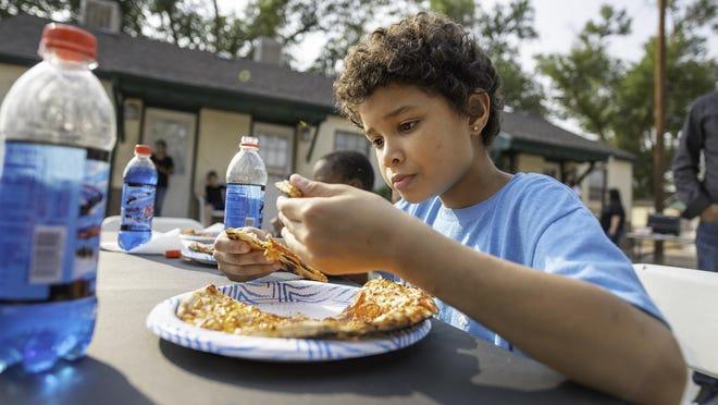 Keontaee, 9, enjoys his SToKD Pizza at Posada's Elko Emegency Family Shelter Friday.
