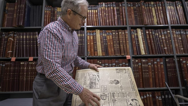 Jon Walker, executive director of the Pueblo City-County Library District, looks through an October 1923 edition of The Pueblo Chieftain in the vault of the Rawlings Public Library on Friday.