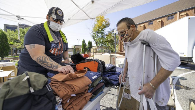 Adrian Medina, Pueblo County veterans service officer, left, helps pick out a shirt and other clothing for Army veteran Mike Laino during the 22nd annual Homeless Veterans Stand Down on Friday outside the First Presbyterian Church, 220 W. 10th St..