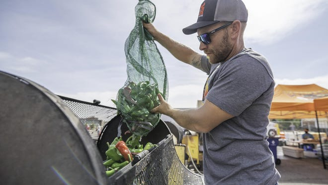 Ryan Richardson prepares to roast a bushel of chiles at the DiTomaso Farms booth Saturday during the Chile and Frijoles Throwback Fest.