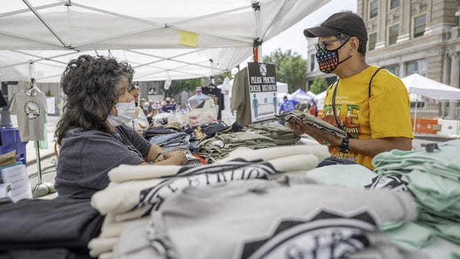 Loretta Rodriguez, of the Greater Pueblo Chamber of Commerce, speaks with Frank Castro about the different T-shirts available for sale during the Chile and Frijoles Throwback Fest on Saturday.