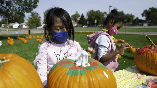 Marcella Losife, left, and Kiara Green, paint their pumpkins Wednesday at the Beulah Heights Elementary schoolyard pumpkin patch.