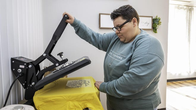 Katie Pickerel, owner of RUTH Productions, uses a heat press to apply a decal onto a shirt Friday at her Midtown Shopping Center location.
