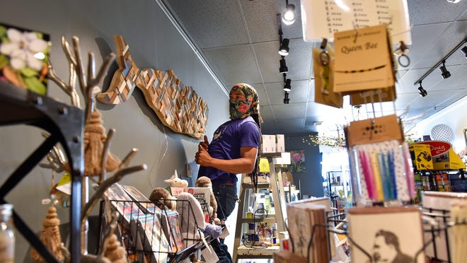 Artist Nate Fontes-Fried takes a closer look at his progress while hanging his wooden sculpture of a sperm whale inside The Hiccup Inc, a creative gift shop, located on Humphrey Street in Swampscott on Thursday, July 9, 2020.