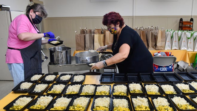 Mary Rawson and Michelle Curreri prepare meals consisting of vegetables, rice and pork in individual servings to be handed out to residents in need as part of the Ellis Square Friends food program at the Living Faith United Methodist Church on Thursday, May 28.