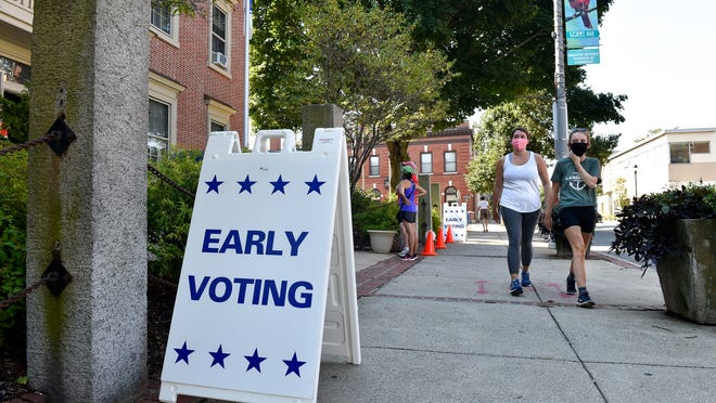 Two people walk by an early voting sign outside Beverly City Hall earlier this year.
