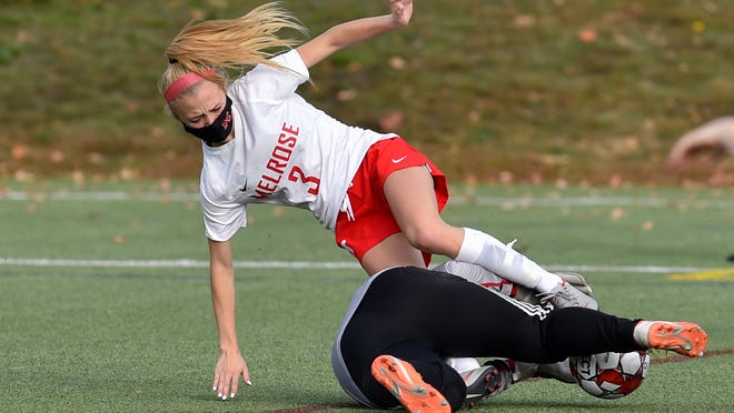 Alyssa Champagne of Melrose gets tripped up by the Wakefield goalkeeper during a game at the Galvin Middle School on Saturday, Oct. 24. [Wicked Local Staff Photo / David Sokol]