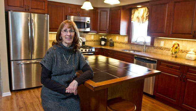 Barbara Kochie sits in a recently remodeled kitchen she designed in Brick.