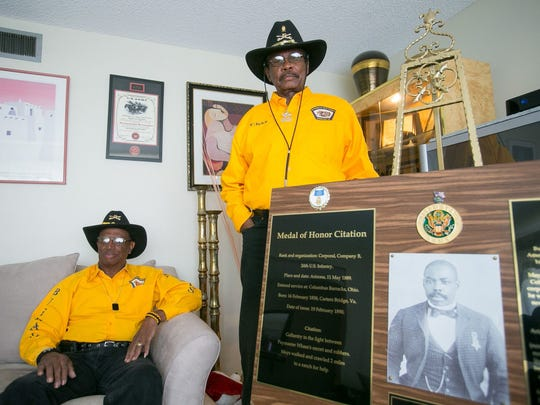"""Buffalo Soldiers Motorcycle Club members Gene Hester, left, and Charles """"Chaz"""" Jackson stand next to a plaque of Medal of Honor recipient Isaiah Mays in Phoenix on Thursday, May 21, 2015."""