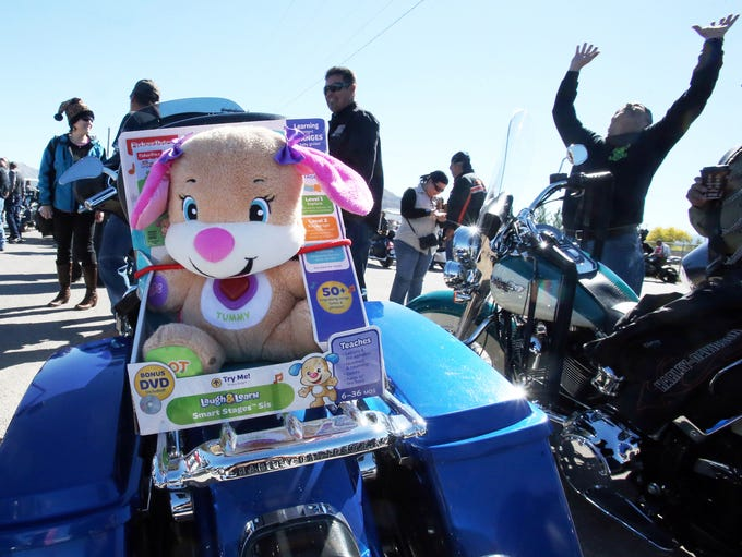 A stuffed animal sits in the back of a motorcycle before